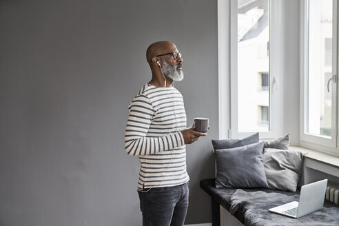 Mature man with earphones drinking coffee - FMKF03753