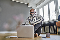 Mature man sitting on floor, working on laptop - FMKF03756