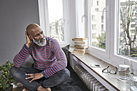 Mature man sitting cross-legged at the window - FMKF03765