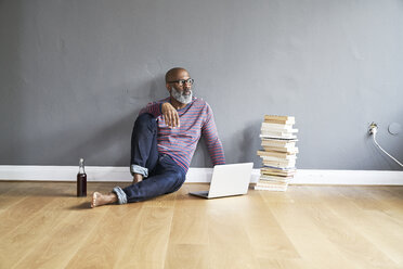 Mature man sitting on floor, using laptop - FMKF03771