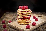 Stack of pancakes with raspberries and raspberry jam on wooden board - LVF06018