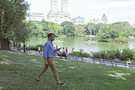 USA, Manhattan, Central Park, man walking with cell phone and earphones on a meadow - BOYF00755