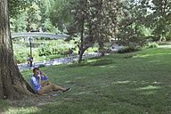 Man sitting on a meadow in a park taking pictures with camera - BOYF00761