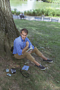 Man sitting on a meadow in a park with notebook - BOYF00764