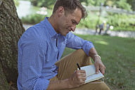 Man with notebook sitting on a meadow in a park writing down something - BOYF00767