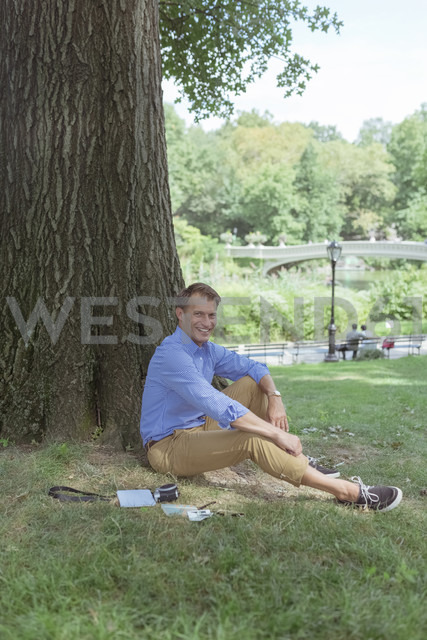 Smiling man relaxing on a meadow in a park - BOYF00773