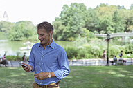 Man using cell phone and earphones in a park - BOYF00776