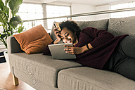 Smiling young woman lying on couch holding credit card and tablet - UUF10315