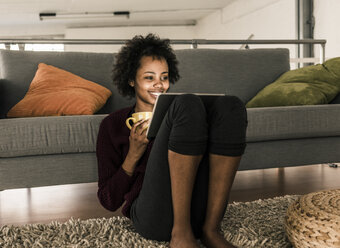 Smiling young woman at home holding cup and tablet - UUF10318