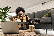 Smiling young woman at home with laptop playing guitar - UUF10324