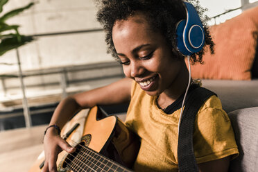 Smiling young woman at home with headphones playing guitar - UUF10327
