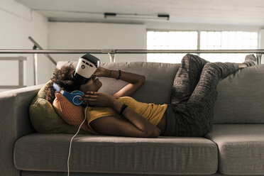 Young woman lying on couch with headphones and VR glasses - UUF10330