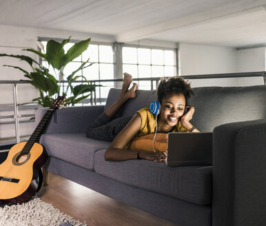 Smiling young woman with headphones lying on couch using laptop next to guitar - UUF10339