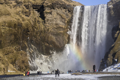 Iceland, people at Skogafoss waterfall with rainbow in winter - MELF00179