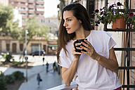 Woman with coffee mug standing on balcony looking at distance - KKAF00659