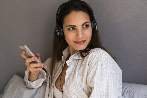 Portrait of smiling young woman with cell phone listening music with headphones at home - KKAF00671