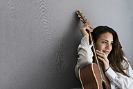 Portrait of smiling young woman with guitar in front of grey background - KKAF00677