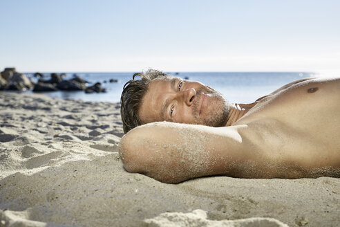 Portrait of man relaxing on sandy beach - PDF01088
