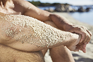 Sandy forearm of man relaxing on the beach, close-up - PDF01091