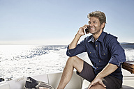 Portrait of smiling mature man on the phonesitting on his motor yacht - PDF01097