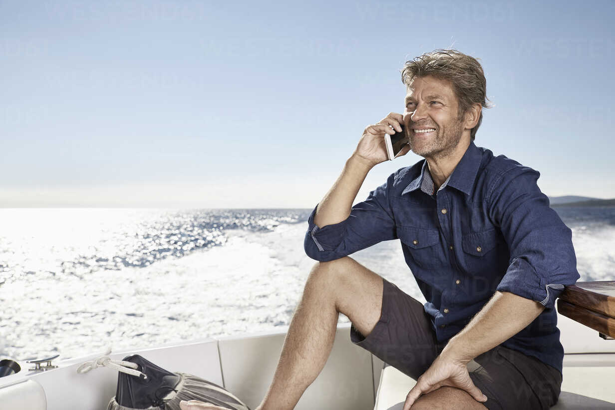 Portrait of smiling mature man on the phonesitting on his motor yacht - PDF01097 - Philipp Dimitri/Westend61