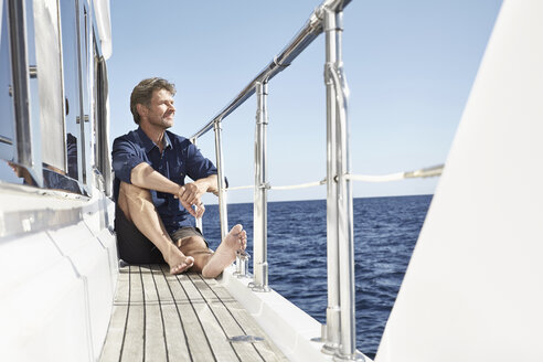 Content mature man sitting on his motor yacht - PDF01100