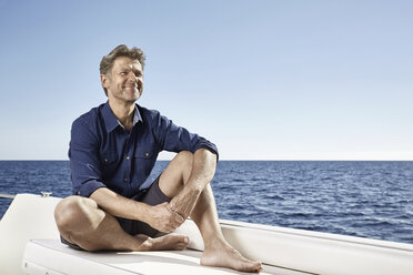 Smiling mature man sitting on his motor yacht - PDF01103