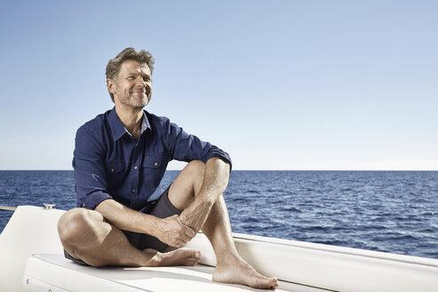 Smiling mature man sitting on his motor yacht - PDF01103