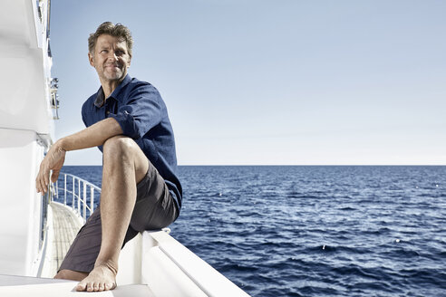 Smiling mature man on motor yacht looking at distance - PDF01106