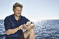 Portrait of smiling mature man in front of the sea using cell phone - PDF01109