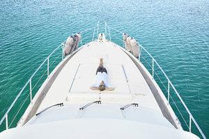 Mature man lying on deck of his motor yacht - PDF01118