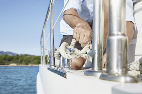 Mature man on motor yacht tying a knot, partial view - PDF01124