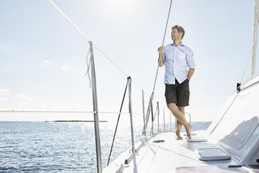 Mature man standing on sailing boat - PDF01130