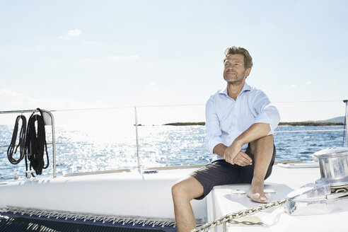 Mature man sitting on his sailing boat - PDF01133