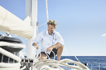 Mature man working with ropes on sailing boat - PDF01136