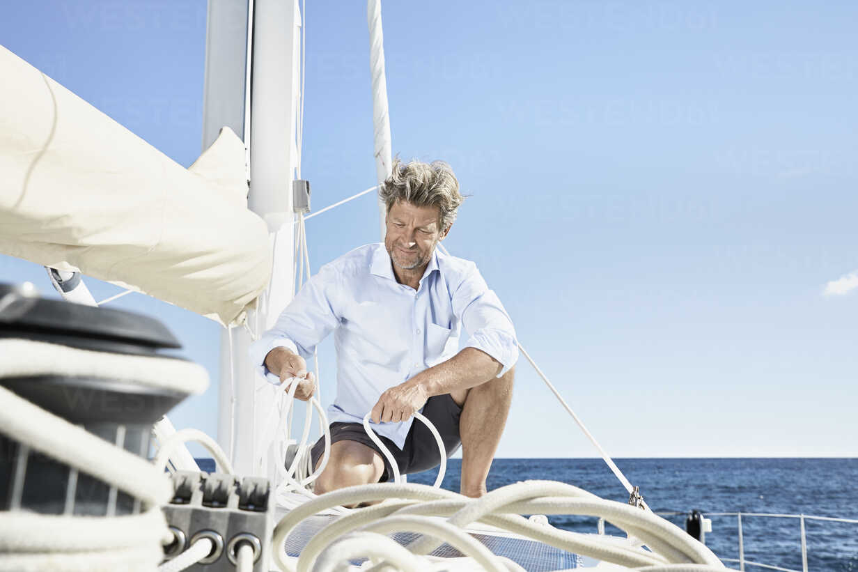 Mature man working with ropes on sailing boat - PDF01136 - Philipp Dimitri/Westend61