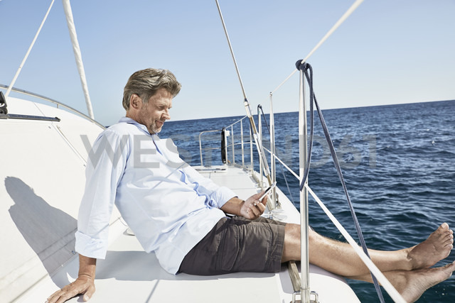Mature man sitting on his sailing boat looking at cell phone - PDF01139 - Philipp Dimitri/Westend61