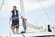 Portrait of smiling mature man on his sailing boat looking at distance - PDF01145