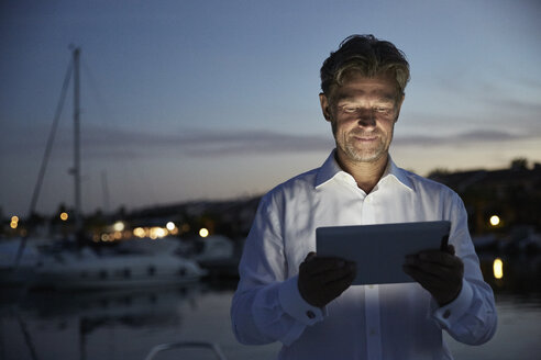 Portrait of smiling mature man standing in front of harbour at evening twilight looking at tablet - PDF01148