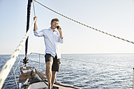 Portrait of smiling mature man on the phone on his sailing boat - PDF01154
