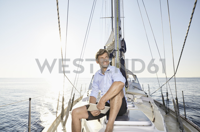 Portrait of smiling mature man with tablet sitting on his sailing boat - PDF01157 - Philipp Dimitri/Westend61