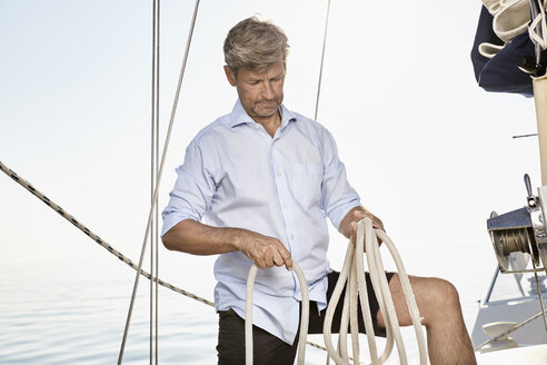 Mature man with rope working on his sailing boat - PDF01169