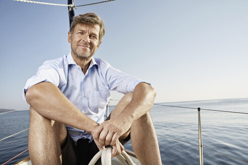 Portrait of smiling mature man sitting on his sailing boat - PDF01172