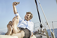 Smiling mature man lying on deck of his sailing boat taking selfie with cell phone - PDF01175