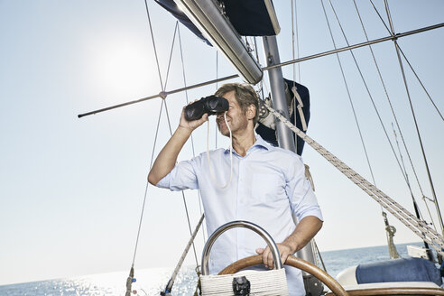 Mature man using binoculars at helm of his sailing boat - PDF01178