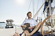 Portrait of happy mature man with tablet sitting on deck of his sailing boat - PDF01181