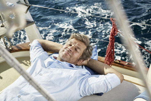 Portrait of smiling mature man lying on deck of his sailing boat - PDF01190