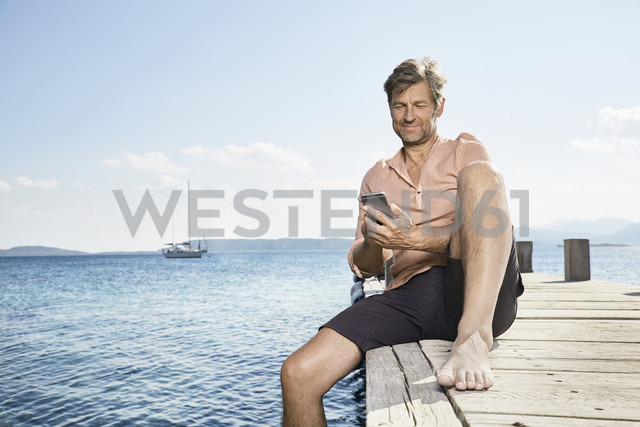 Smiling man sitting on jetty using cell phone - PDF01196 - Philipp Dimitri/Westend61