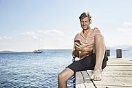Smiling man sitting on jetty using cell phone - PDF01196