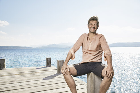 Portrait of smiling man sitting on jetty - PDF01205
